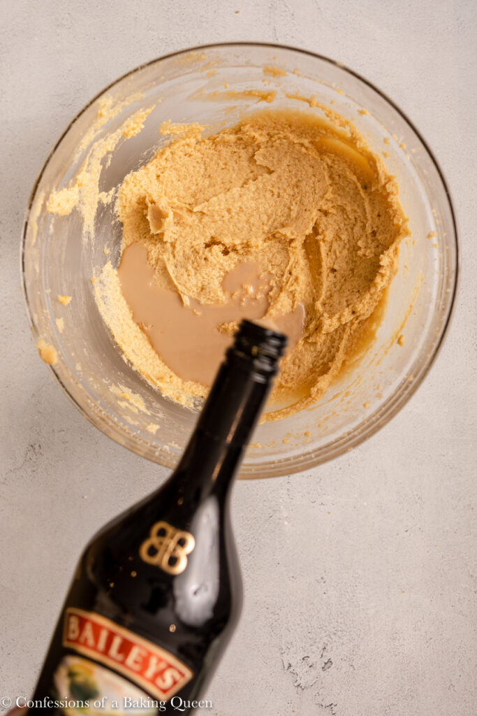 baileys added to wet ingredients in a glass bowl on a light grey surface