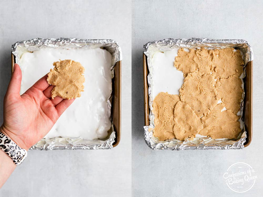 hand holding a piece of cookie dough pressed into a square then laid on top of marshmallow creme in a foil lined square pan on a grey surface