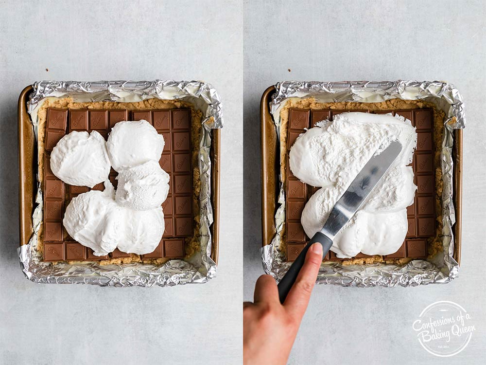 marshmallow creme spread with a spatula on top of chocolate bars on top of cookie dough in a foil lined square baking pan on a grey surface