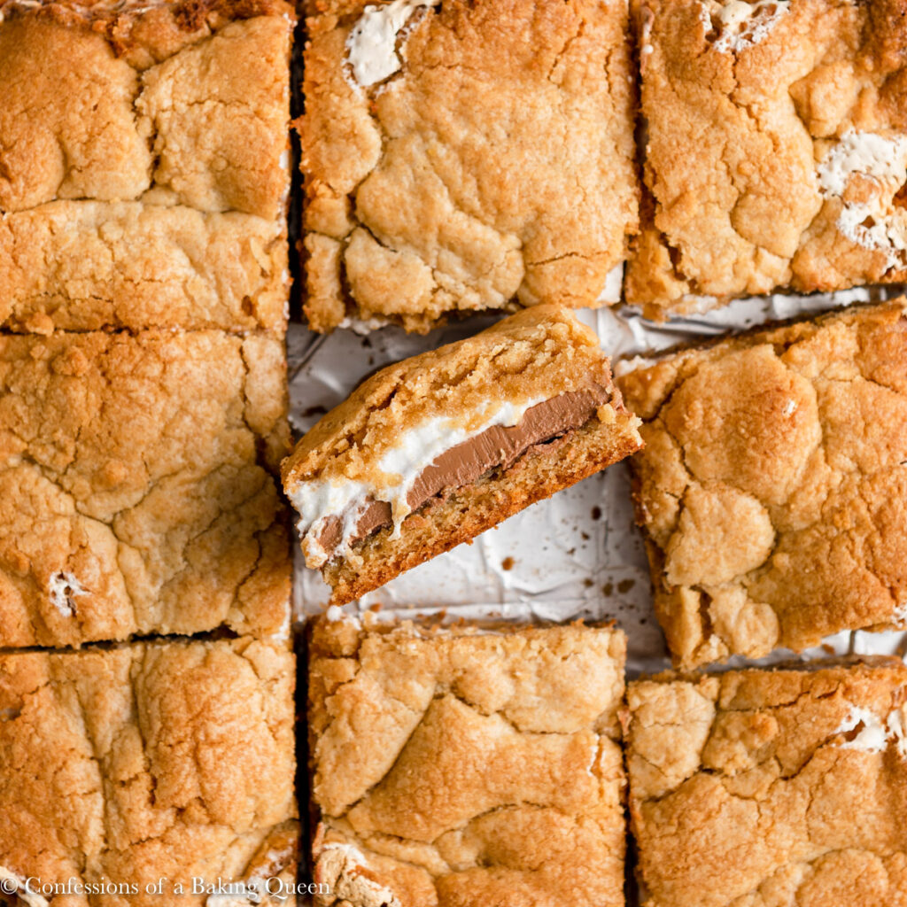 smores bars cut into squares with the middle one sticking up showing the layers