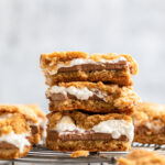 s'mores bars stacked on top of each other on a wire rack on a grey surface