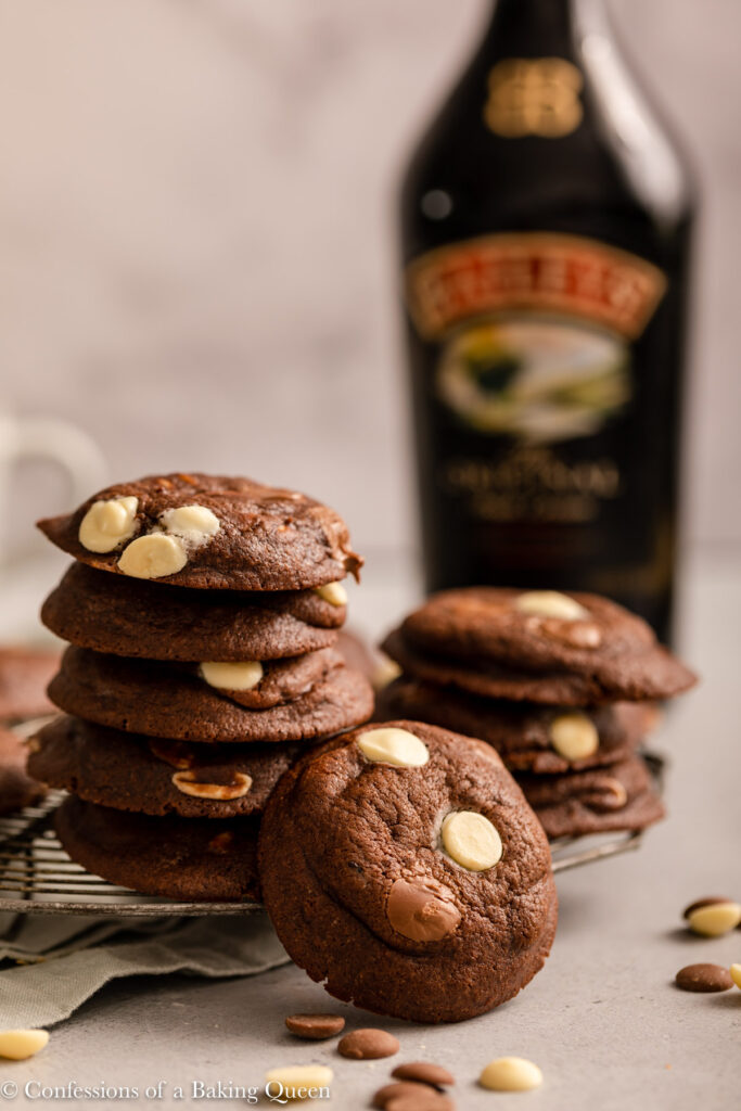 stack of baileys chocolate chip cookies on a light grey surface on a wire rack next to a bottle of baileys irish cream on a light grey surface