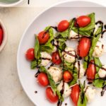 plate full of caprese skewers with balsamic glaze on top