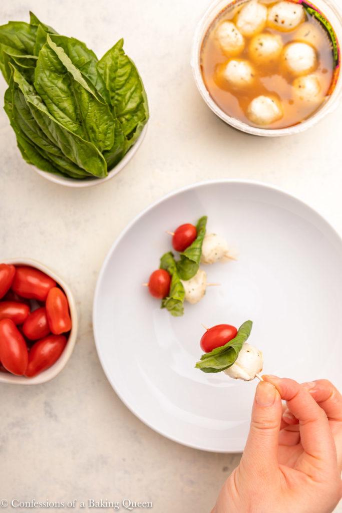 hand holding a tomato mozzarella basil skewer