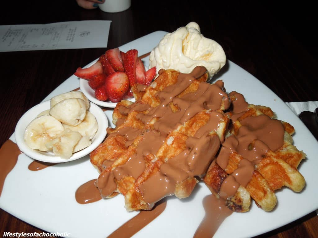 waffles on a plate with melted chocolate bananas strawberries and ice cream