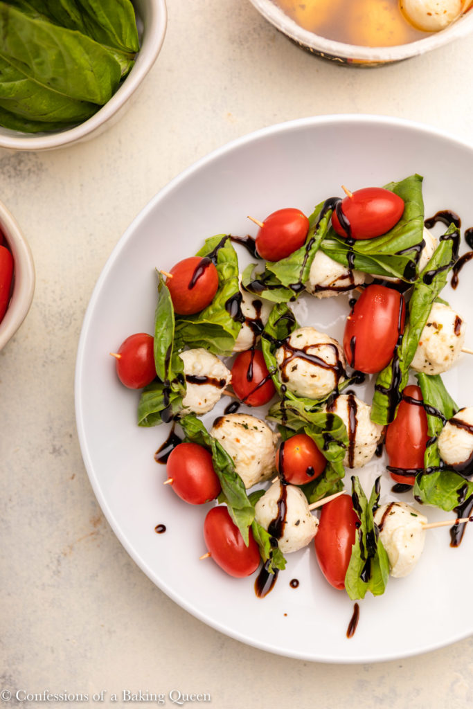 plate full of tomato mozzarella basil skewers with balsamic glaze on top