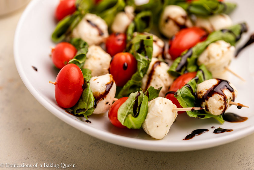 plate of caprese skewers with balsamic glaze