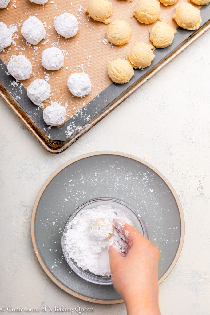 hand rolling cookie dough ball in powdered sugar and putting on a baking tray