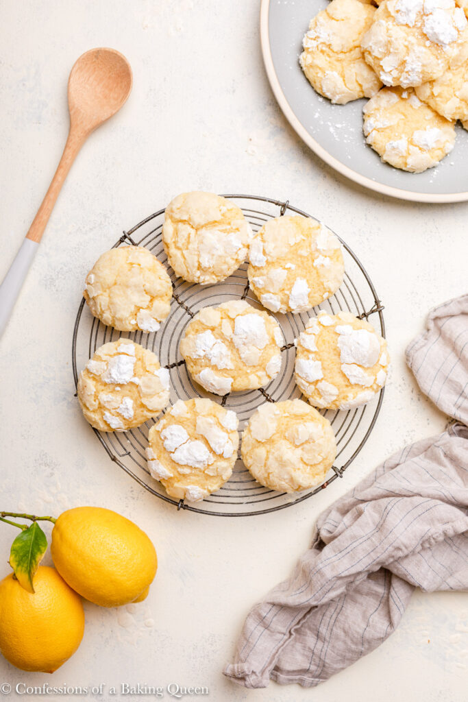 lemon crinkle cookies cooling on a wire rack next to a plate of cookies, lemons, dishtowel and a wooden spoon