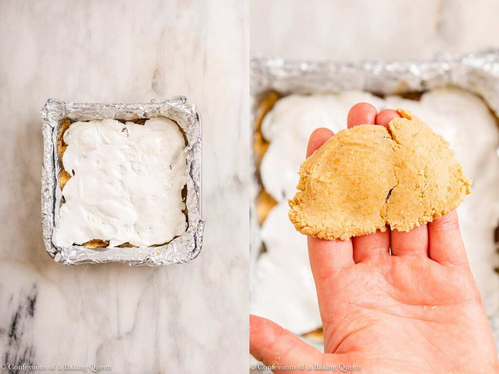 marshmallow layer spread thin and graham cracker pressed into a layer in a foil lined baking pan on a marble surface