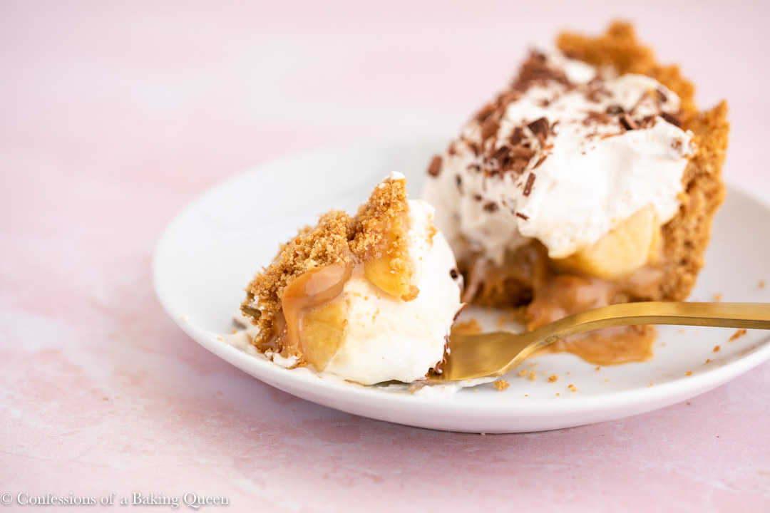 a bite of banoffee pie on a gold fork on a white plate