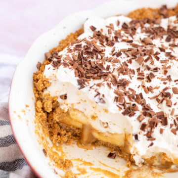 banoffee pie in a ceramic pie dish with a slice missing