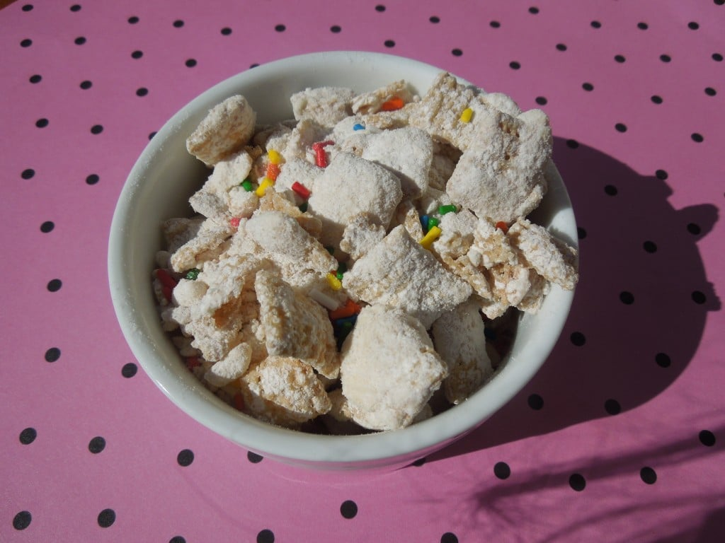 cake batter puppy chow in a white bowl on a pink and black polka dot background