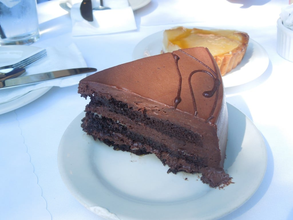 A piece of chocolate cake on a white plate from Andersen\'s danish bakery in Santa barbara