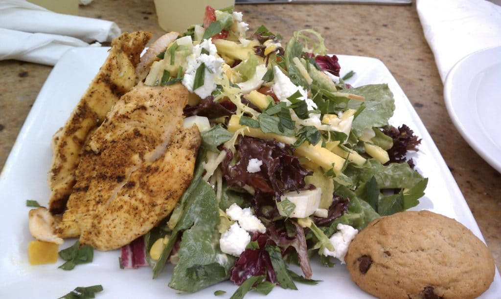 seasonal salad with a small cookie on a white plate from PDM