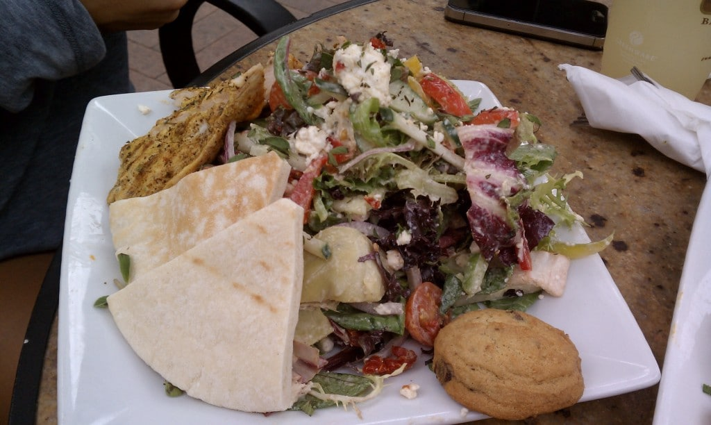 mediterranean salad on a white plate with a cookie from PDM