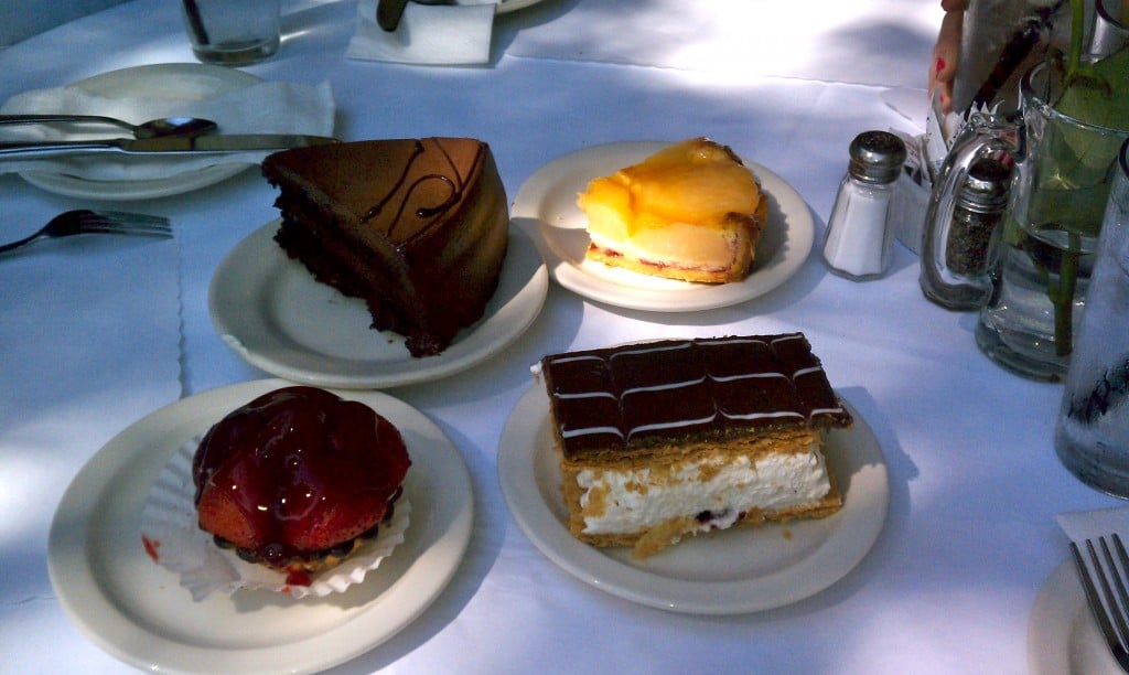 four different desserts on separate plates on a restaurant table