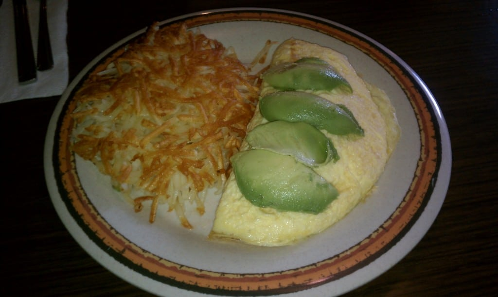 omelette with avocado on top with has browns