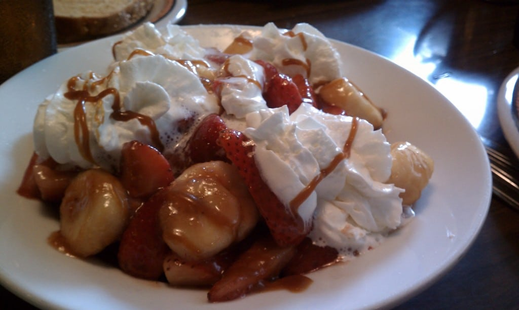 beignets with caramel strawberries and whipped cream in a large white bowl on a table