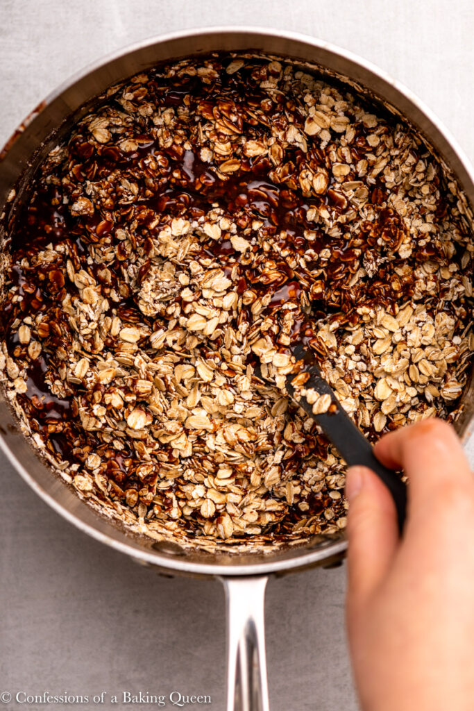hand mixing oats into chocolate mixture in a metal pot