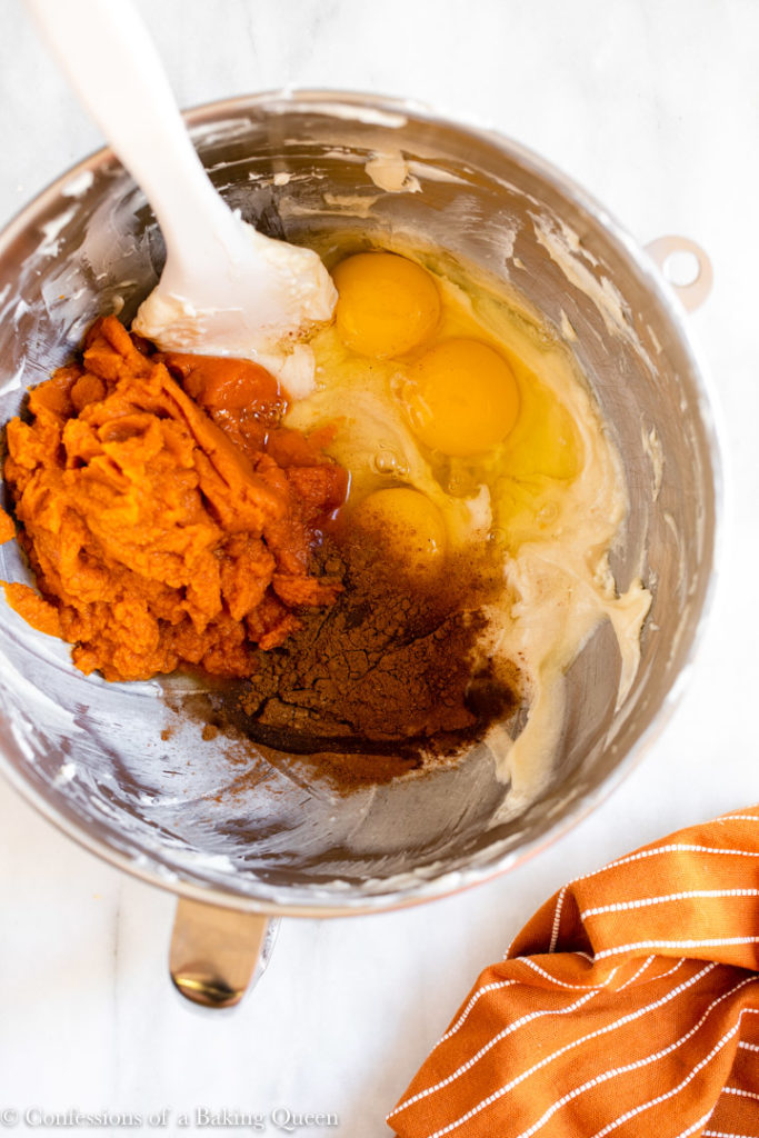 pumpkin puree, eggs, and spices added to cream cheese mixture in a metal bowl