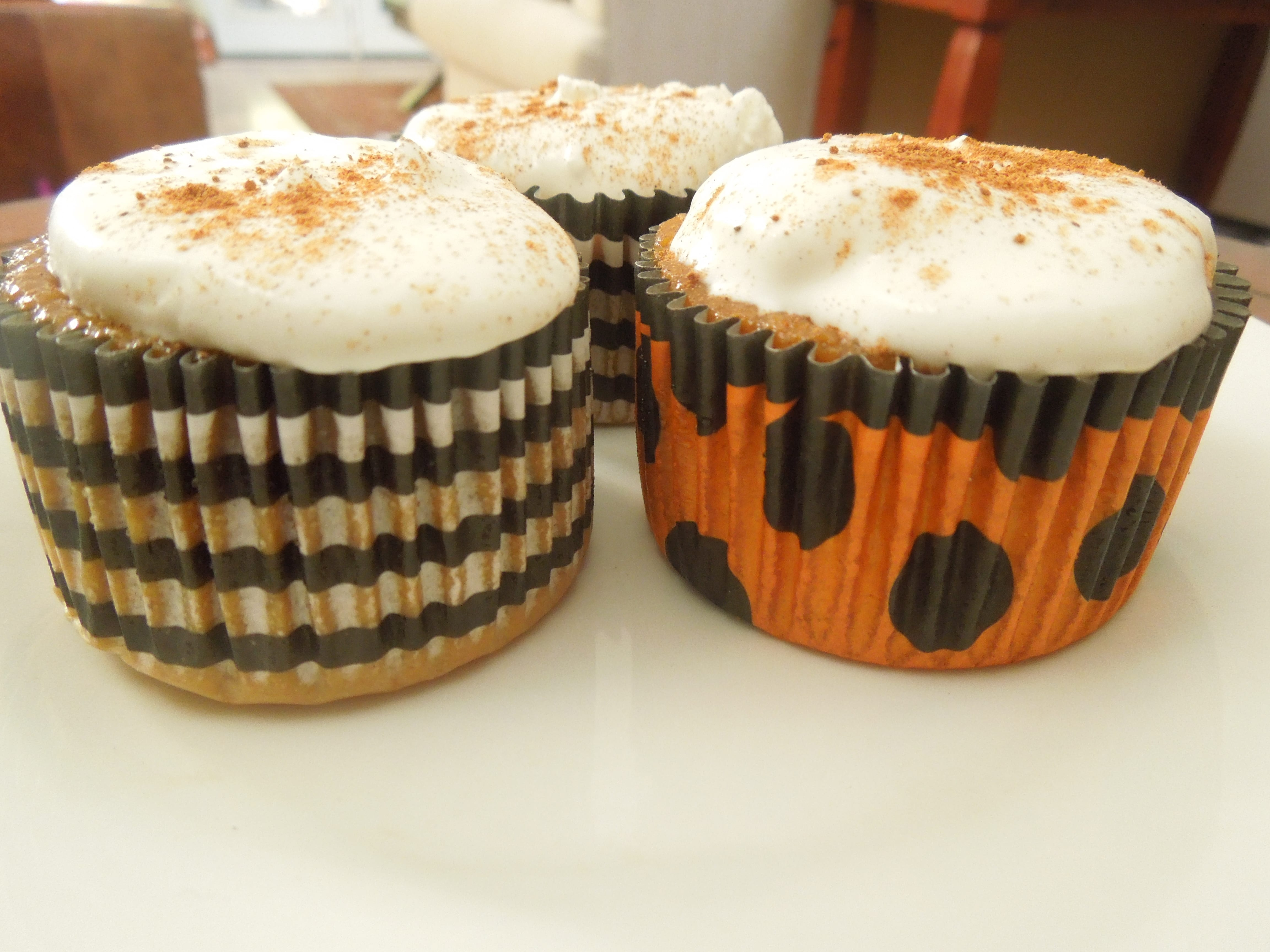 Pumpkin Pie Cupcakes with whipped cream in halloween black white and orange cupcake liners on a white plate