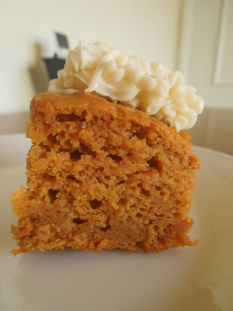 pumpkin bar with cream cheese frosting side angle on a white plate