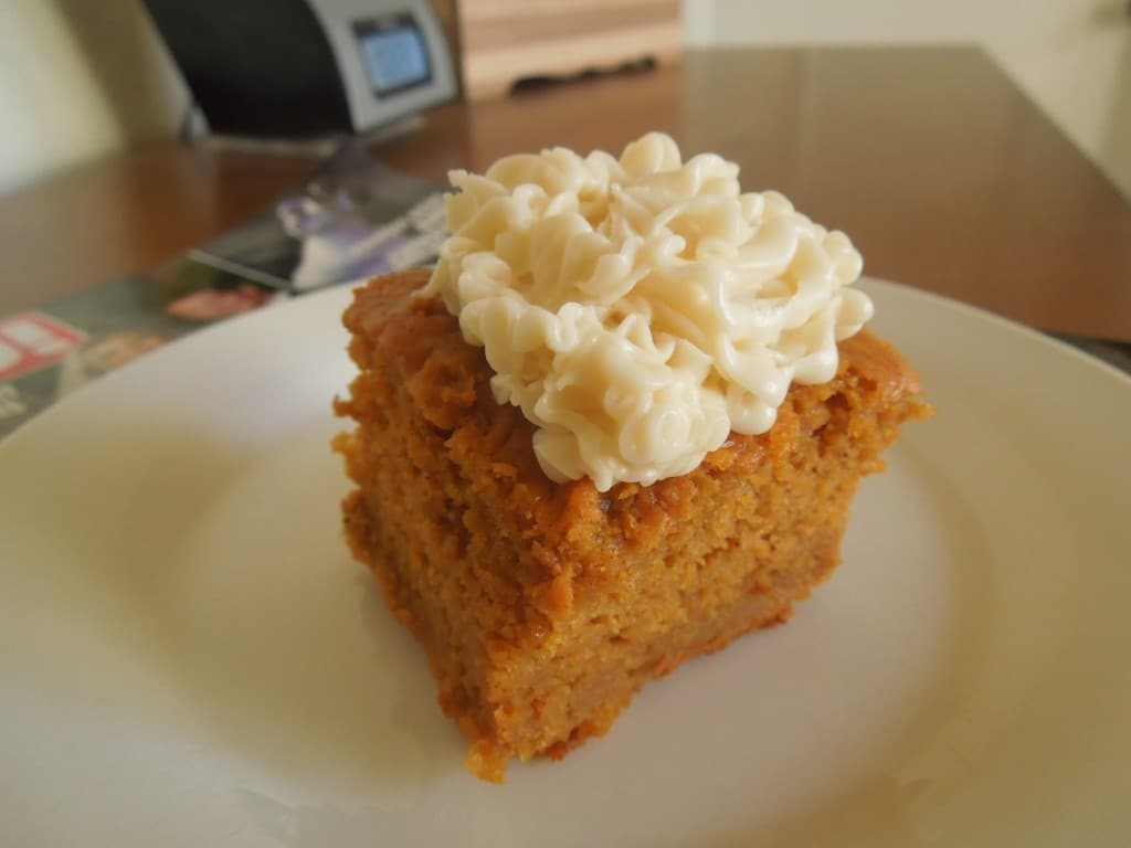 overhead angle of pumpkin bars with cream cheese frosting on a white plate