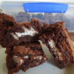 Peppermint Patty Stuffed Brownies stacked on top of each other on a white plate on a wood table