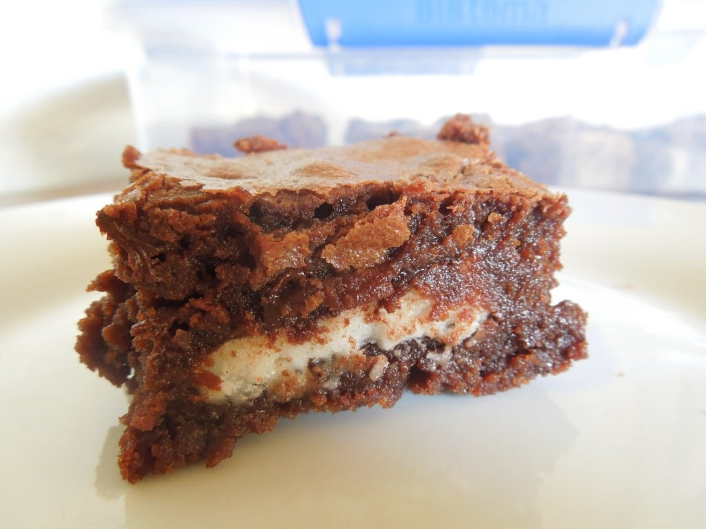 up close of peppermint patty stuffed brownies showing white filling inside brownie sitting on a white plate with a container of more brownies in the background