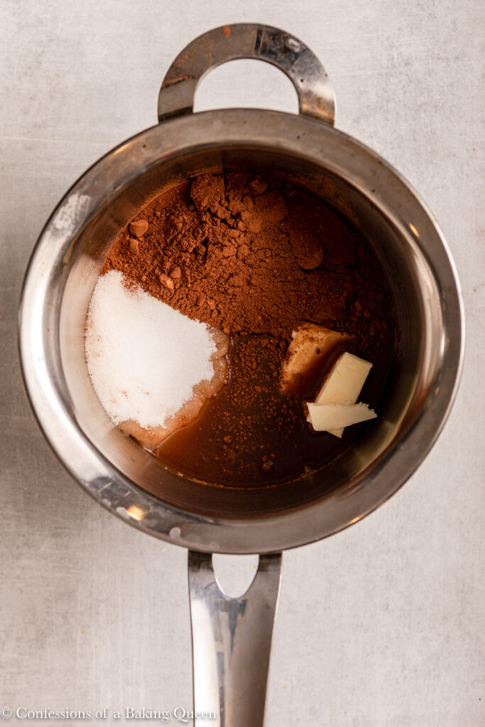 cocoa powder, sugar, butter, and water in a metal pot on a light grey surface