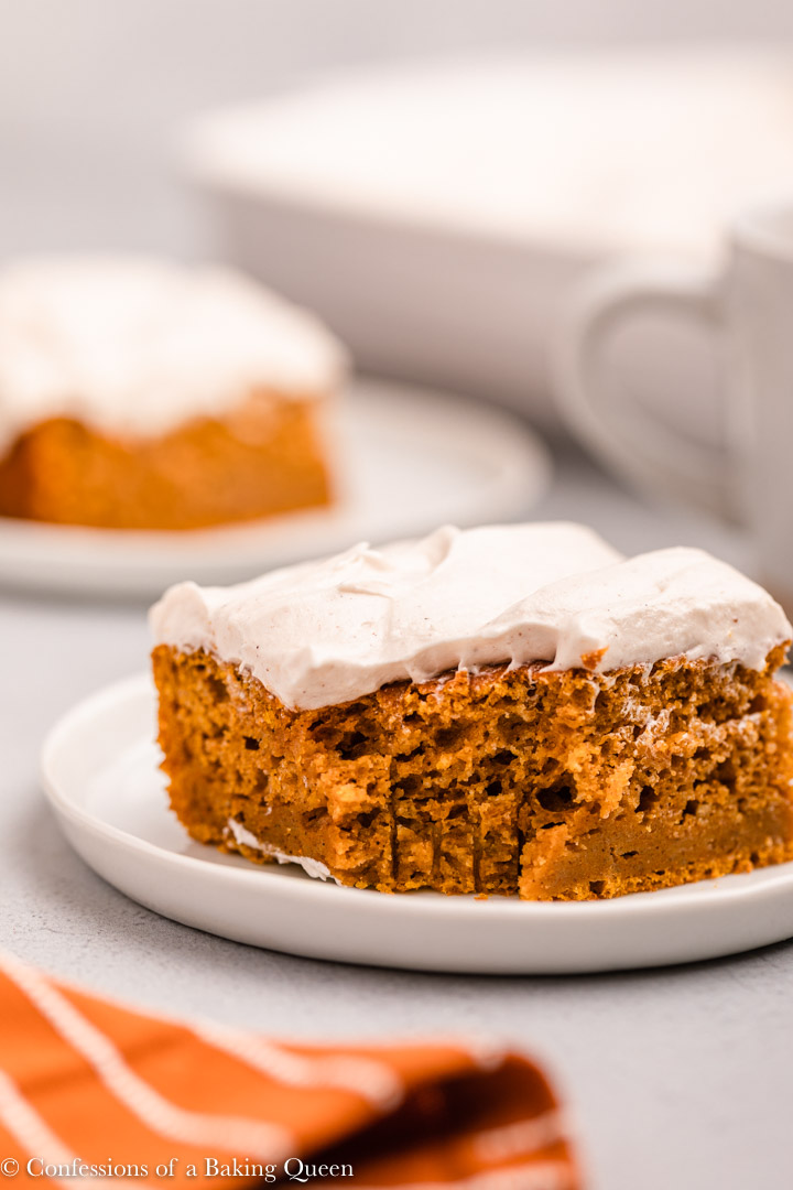 pumpkin bars with cream cheese frosting on white plates on a grey background
