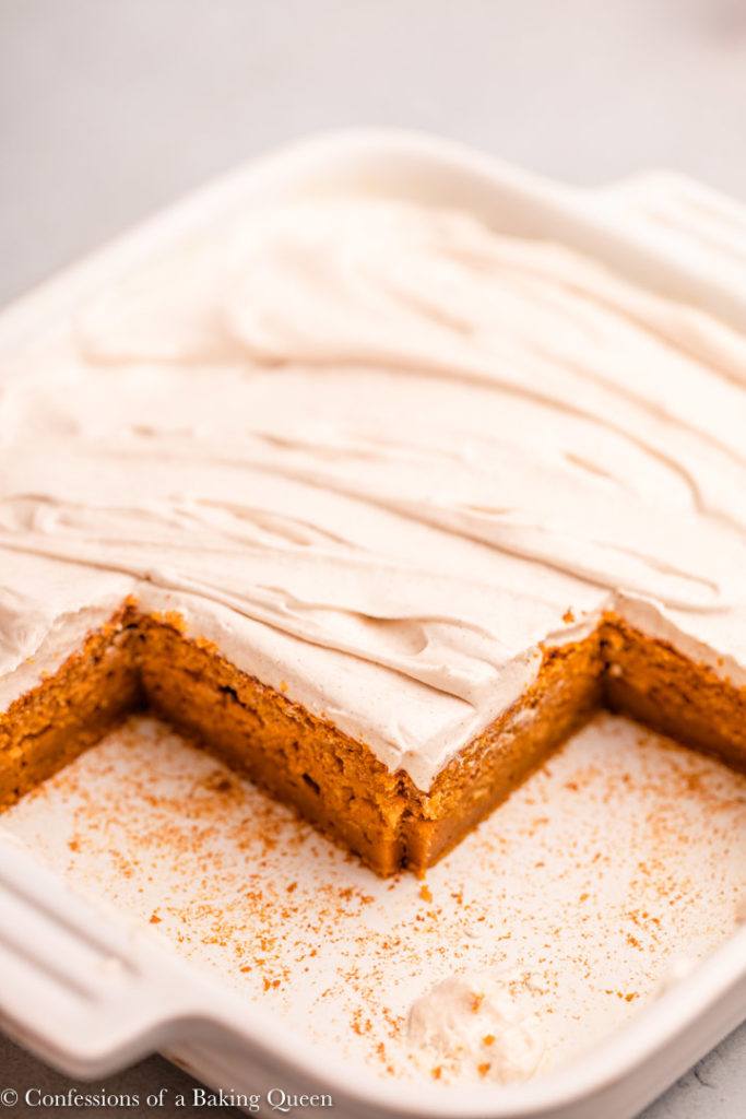 pumpkin bars with cream cheese frosting in a white ceramic dish
