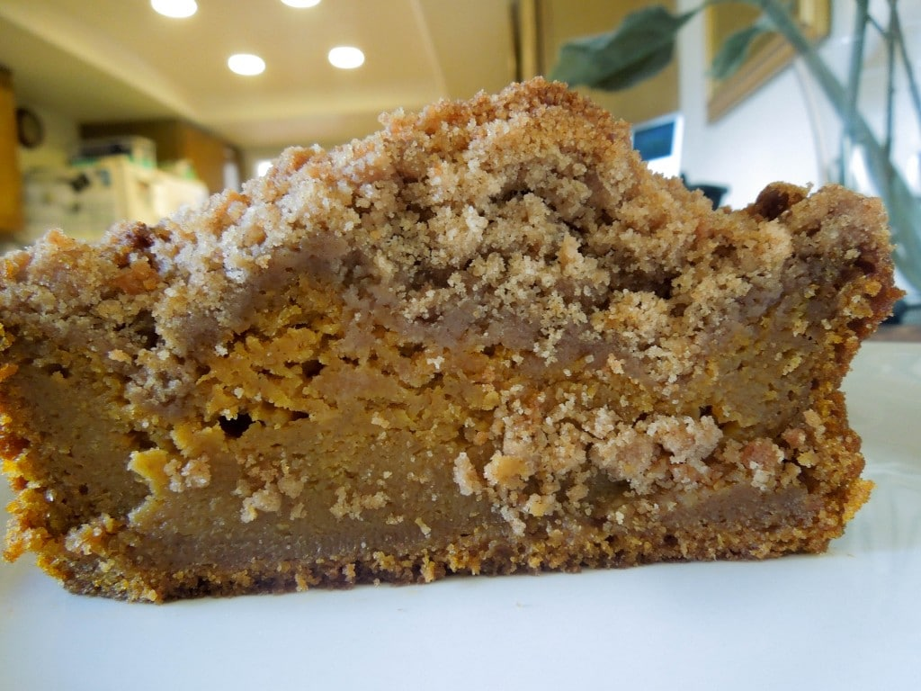 up close of cut open pumpkin bread on a white plate in the kitchen