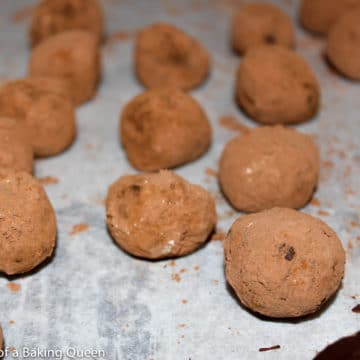Bailey's Truffles rolled in cocoa powder on a parchment lined baking sheet