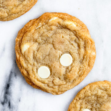 three white chocolate cookies on a marble surface