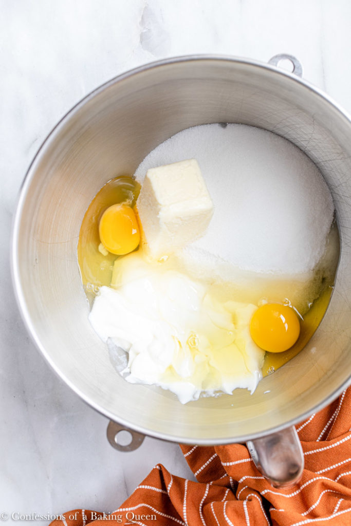 sugar, butter, eggs and sour cream in a metal mixing bowl for a banana bars recipe