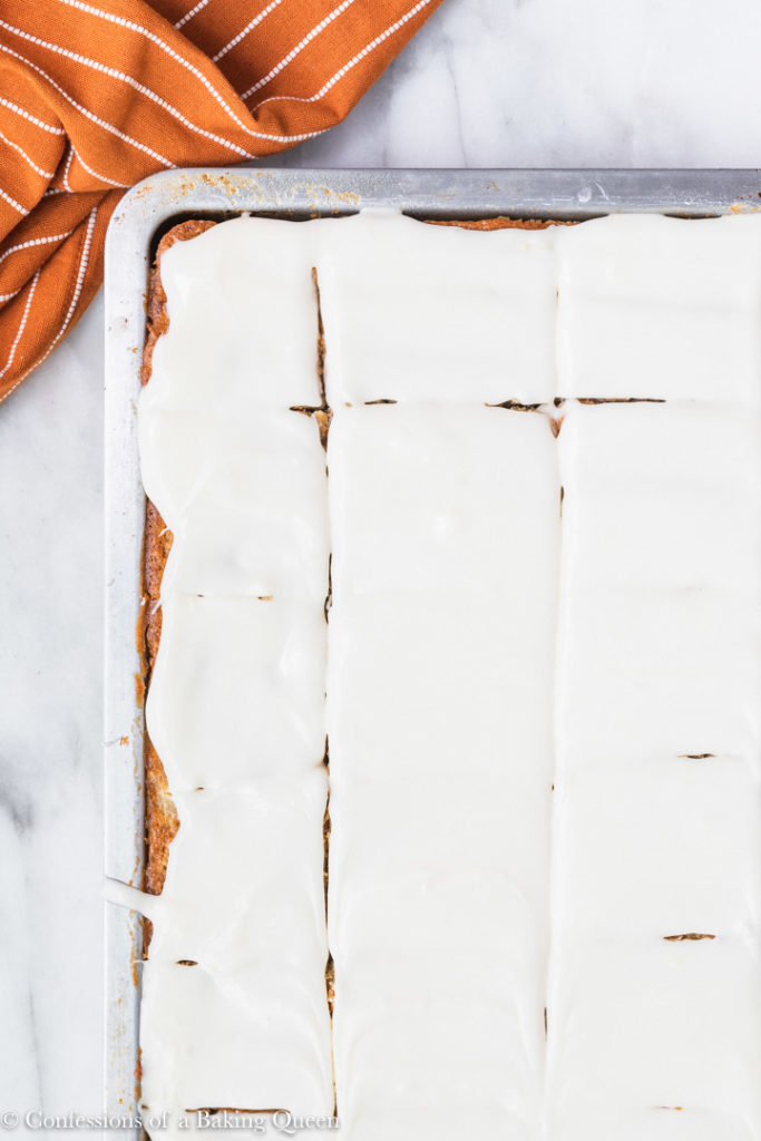 banana bars with cream cheese frosting cut into chunks in a metal baking pan