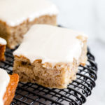 banana bars with cream cheese frosting on top of a black rack