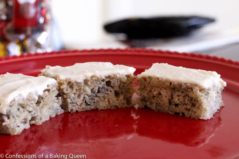 three banana bars with cream cheese frosting on a red plate