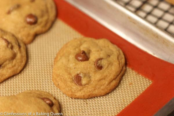 brown butter chocolate chip cookies baked on a silpat lined baking sheet cooling on a wire rack