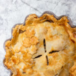 clove apple pie baked in a grey pie dish on a white and grey surface