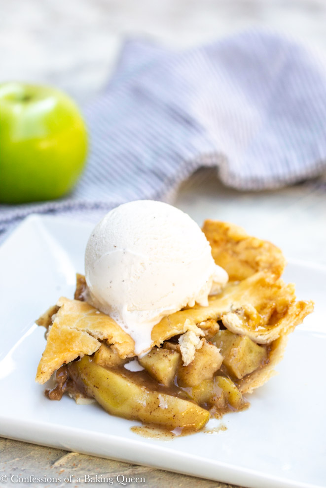 clove apple pie slice with a scoop of vanilla ice cream on top on a white square plate with a green apple in the background and a blue linen on a white background