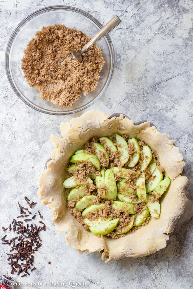 brown sugar and clove mixture in a small bowl and pie crust in a pie dish with slices of apple with more sugar on top on a grey surface