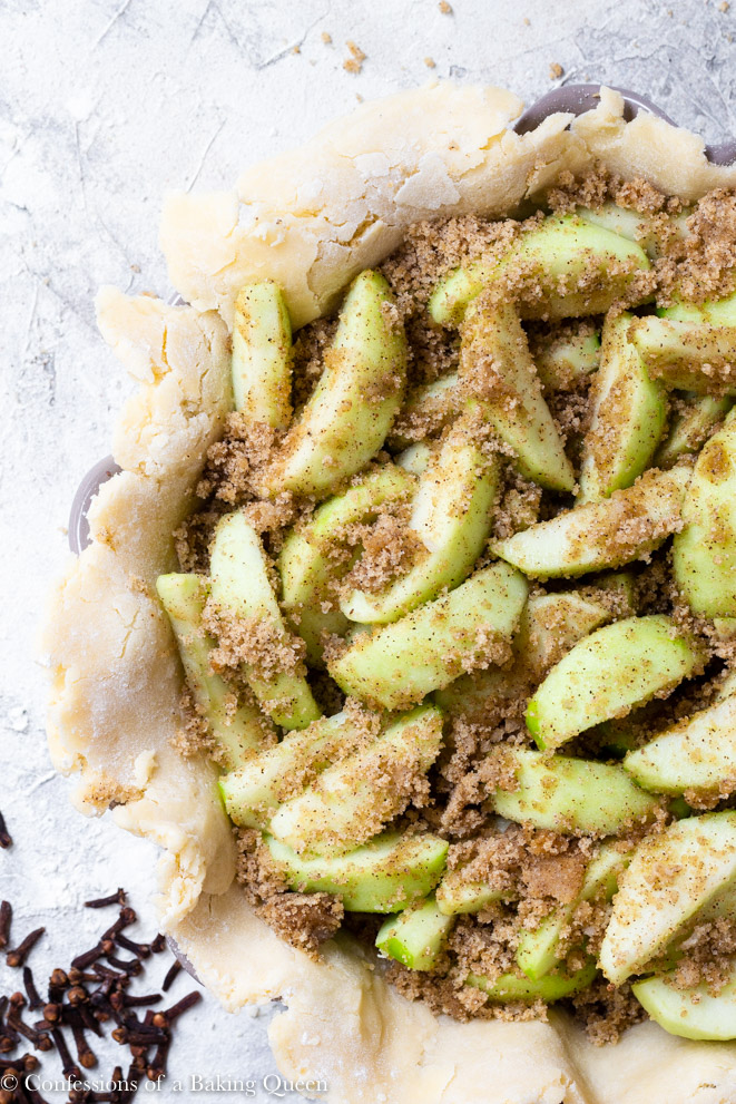 apples with brown sugar and cloves inside pie crust on a grey surface