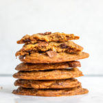 cookie butter sea salt chocolate chip cookies stacked on top of each other on a white marble surface