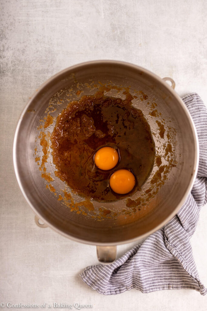 egg and egg yolk added to butter sugar mixture in a metal mixing bowl on a light grey surface with a blue linen