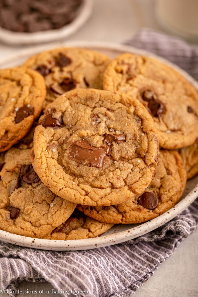 plate of sea salt chocolate chip cookies on top of a blue linen on a light grey surface with a cup of chocolate in the background