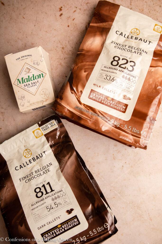 bags of callebaut chocolate and maldon sea salt on a light brown surface