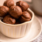 bowl of sea salt chocolate truffles on top of a plate and a white linen on a light brown surface with a cup of coffee in the background